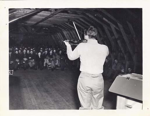 Menuhin playing for the assembled troops in a Shemya quonset hut.