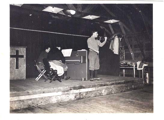 Menuhin between pulpit and pinball machine, playing for the troops
